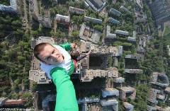 آویزان شدن یک جوان 24 ساله از بلندترین ساختمان تجاری جهان!/به رخ کشیدن آمادگی جسمانی به قیمت بازی با جان!