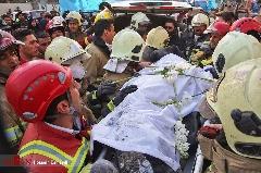 آتش نشانان ایستاده بر روی آوار پلاسکو، یاران شهید خود را با دسته گل بدرقه می کنند